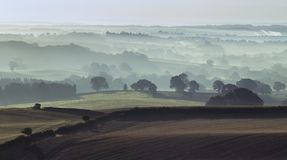 Misty Fields of British Countryside at Autumn. Morning mist over farming fields at autumn. Much Wenlock in Shropshire, UK royalty free stock photography