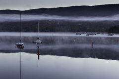 Morning mist over a lake with boats Stock Photos