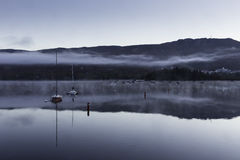 Morning mist over a lake with boats Royalty Free Stock Photo