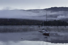 Morning mist over a lake with boats Royalty Free Stock Image