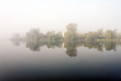 Morning mist over the lake with reflection in the water. Fog on a river Royalty Free Stock Photography