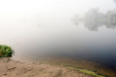 Morning mist over the lake with reflection in the water. Fog on a river Royalty Free Stock Images