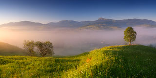 Morning mist over a mountain village Stock Image