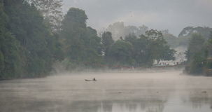 Morning mist over water. Boat disappearing in mist. Morning fog over water stock footage