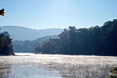 Morning Mist Rising From Lake. Morning mist rising off lake with blue mountains in the background Stock Image
