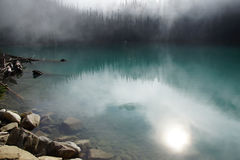 Morning mist rising from  turquoise lake Royalty Free Stock Image