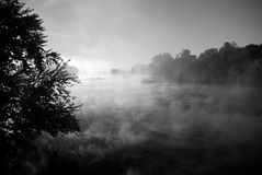 Morning mist on river. A gray tone view of early morning mist rising from a quiet river Stock Photography