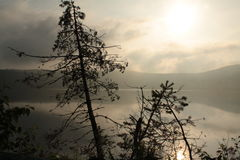 Morning mist slowly fades as the sun warms the air. Photo taken at 06:00. Lac ouimet in Mont Tremblant, Quebec Canada Stock Photography