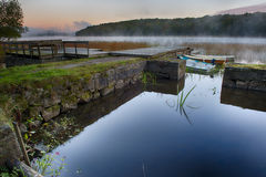 Rowboats in morning mist. A small harbor with rowboats in a lake as the morning mist is rising Stock Image
