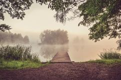 Morning misty landscape on the lake. Wooden pier and island with trees on the lake royalty free stock image