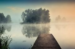 Morning misty landscape on the lake. Wooden pier and island with trees on the lake stock photos