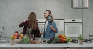 In the morning in a modern kitchen, couple have a good mood before starting to prepare breakfast they listen music and. Happy dacing and singing using kitchen stock video