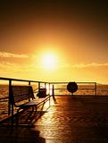 Morning on mole in harbor, empty bench. Tourist  pier construction above sea. Royalty Free Stock Image
