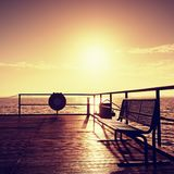 Morning on mole in harbor, empty bench. Tourist  pier construction above sea. Royalty Free Stock Images