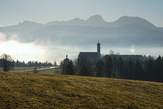 Morning mood in the Alps. Scenic bavarian church, southern bavaria near Irschenberg, the Apls in the background Royalty Free Stock Photo