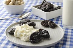 Closeup of plate with cottage cheese. prunes, peanuts on table. Delicious dieting dinner served on blue checkered tablecloth royalty free stock photo