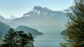 Morning mountain range lake landscape. Static medium long high dynamic range shallow depth of field shot of of Alps shoring Lake Lucerne during a hazy sunny stock video footage
