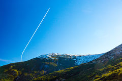 Morning Mountain View and Airplane Vapor Trail on Deep Blue Sky Stock Photos