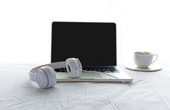Morning music background. Coffee with laptop in white bed, sheet, duvet and pillow, messed up. Stock Image