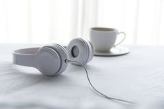 Morning music background. Coffee in white bed, sheet, duvet and pillow, messed up. Royalty Free Stock Photo