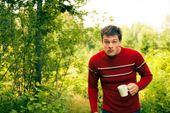 Young man in nature with a mug of coffee Stock Image