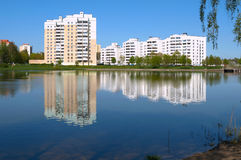 Morning near the city lake. The small semi-lake in the city. On the opposite side there are the multi-storey town houses, cars near the houses . green trees Royalty Free Stock Images