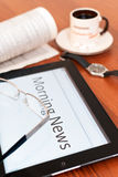 The morning news. Tablet PC, a cup of coffee, a newspaper and watch on the table Royalty Free Stock Photo