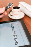 The morning news. Tablet PC, a cup of coffee, a newspaper and watch on the table Stock Image