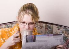 Morning news with coffee. Young lady enjoying an early morning coffee and newspaper royalty free stock image