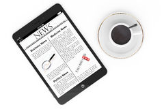 Morning news concept. Modern Tablet pc and cup of coffee Stock Photos