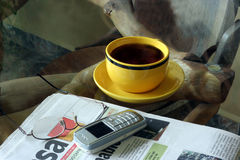 Morning Newspaper. A table with newspaper,cellphone, glasses and a cup of coffee Stock Images