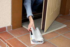 Morning newspaper. Woman picking up morning paper through the open door Royalty Free Stock Photo