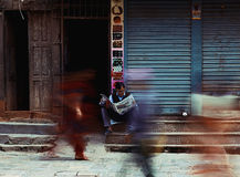 Morning Newspaper. A man reading the morning paper in the middle of the busy street of Kathmandu Royalty Free Stock Photography
