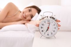 Free Morning Of Beautiful Young Woman Turning Off Alarm Clock While Lying In Bed Stock Photos - 150061743