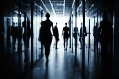 Morning in office building. Silhouettes of several business people in corridor of office building Royalty Free Stock Photography
