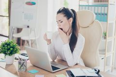 Morning in the office. Young pretty business lady lawyer is yawn. Ing at her work place with cup of coffee in the hand, in smart outfit, with glasses stock images