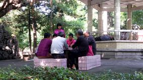 Old people playing cards in the park leisure stock footage