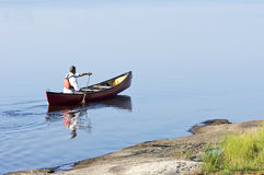 Morning Paddle in a Red Canoe. A man out for an early morning paddle in a canoe on Georgian Bay - Ontario, Canada Stock Photography