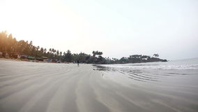 Morning at Palolem beach. People jogging at Palolem beach Goa, India stock footage