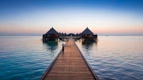 Morning. Panorama of tropical island resort with overwater bungalows at night. Maldives. Ari Atoll Royalty Free Stock Image