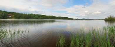 Morning panorama view over lake from fishing place to opposite bank, reflection of sky in the water level. Royalty Free Stock Photo
