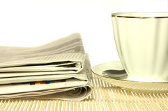 Morning paper and cup of coffee. Over yellow mat Royalty Free Stock Image