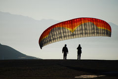 Morning Paragliding Prep. Two paragliders wait for enough wind to launch in the early morning light Royalty Free Stock Photos