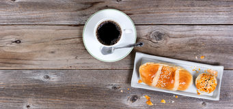 Morning pastry meal and dark coffee on rustic table. Freshly baked pastries with dark coffee on rustic wooden table. Flat layout with copy space royalty free stock photo