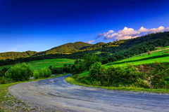 Morning path to mountains. Empty winding mountain road on a hillside in the early morning Royalty Free Stock Photography