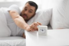 Close up of man in bed reaching for alarm clock. Morning and people concept - close up of sleepy young man in bed reaching for alarm clock on bedside table at royalty free stock photo