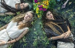 Pagan women lying on the grass. Morning photo session in the forest Stock Image