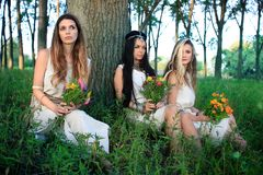 Morning photo session in the forest with three pagan women. Three pagan women sitting by the tree Royalty Free Stock Image