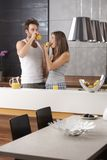 Morning picture of young couple. In the kitchen with apple and orange juice Stock Photos