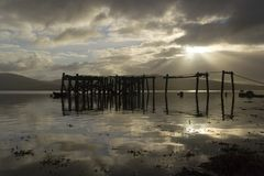 Morning pier. A ruined pier reflected in the calm of a morning seashore royalty free stock photography